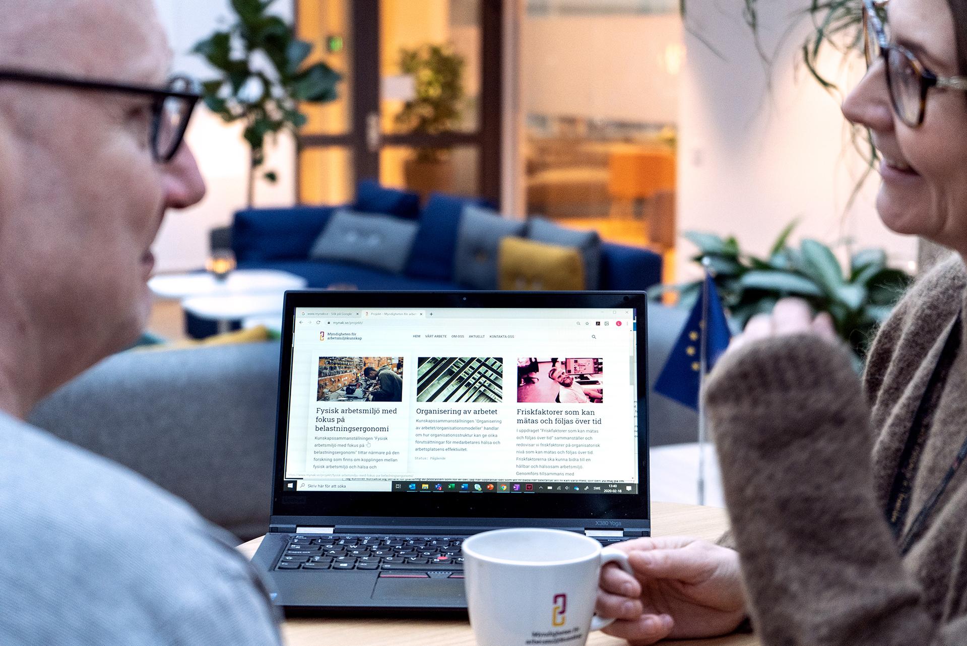 Medarbetare i fikarummet framför en laptop som visar upp myndighetens hemsida.