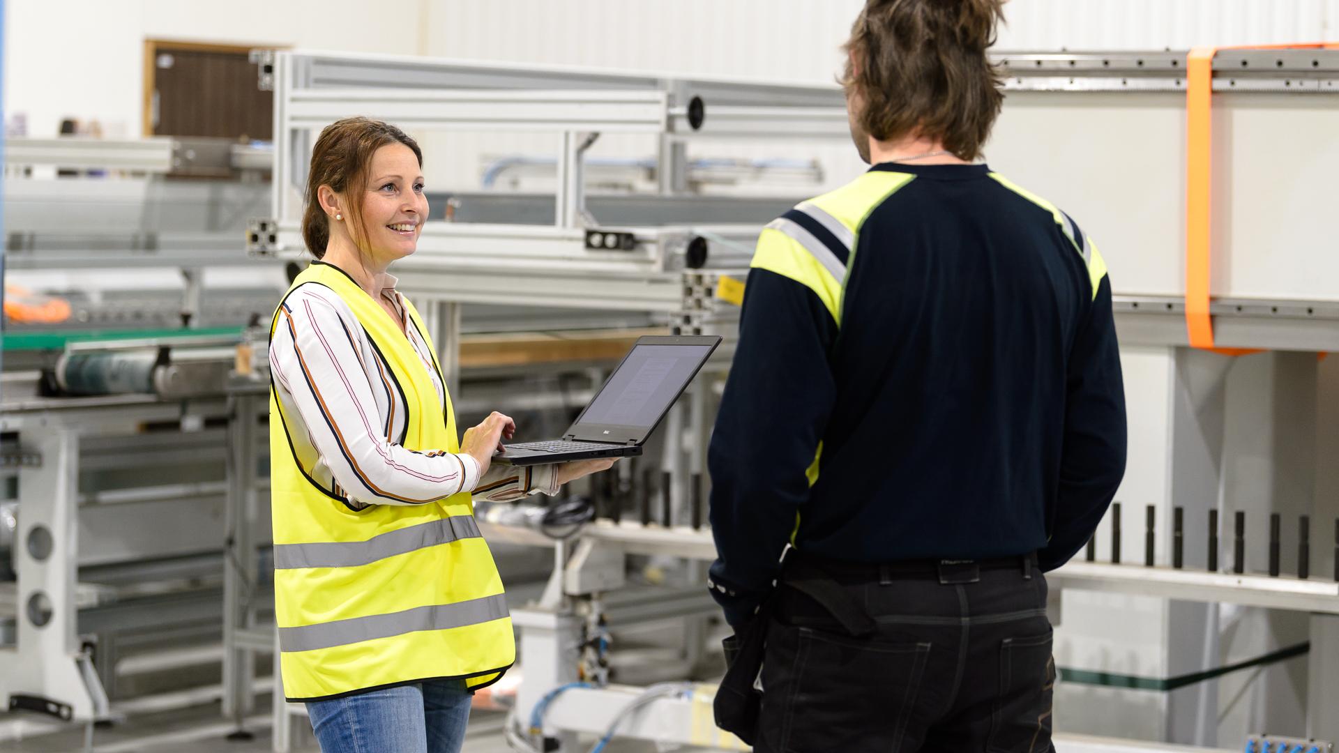 Bild på två personer i industrimiljö.